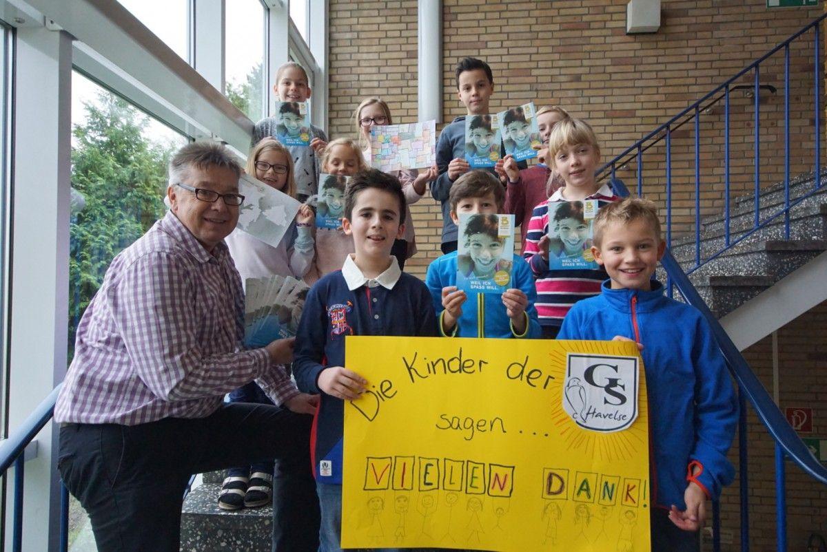 Klassensprecherinnen und Klassensprecher der Grundschule Havelse freuen sich über den Besuch aus Neustadt und haben sogar ein kleines Dankeschön-Plakat gemalt. Heino Lohmann, Betriebsleiter des Balneons (links), übergibt insgesamt 50 Gutscheine.